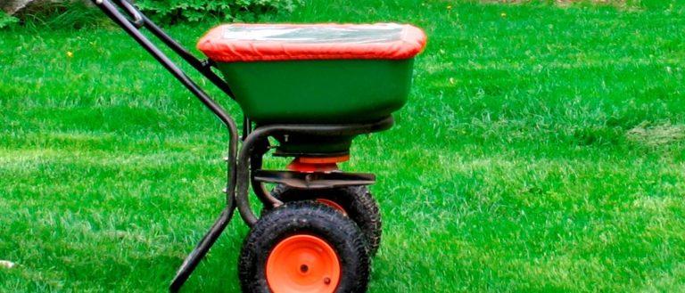 A seed fertilizer sitting on a lawn.