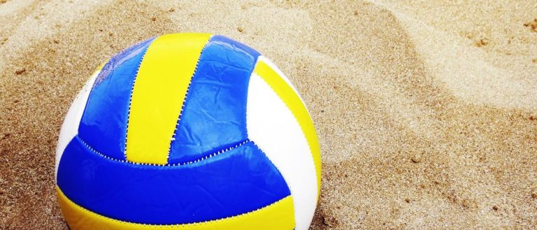 A volleyball resting on the sand.