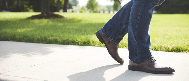 Man walking on sidewalk next to bright green grass.