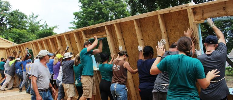 A line of Habitat for Humanity volunteers pushing up a wall.