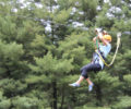 A person going down a zipline during a Zipping for Autism event.