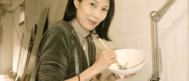Artist Reiko Miyagi in a workshop painting a bowl.