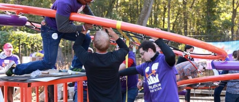 """Workers assembling a """"Build It with KaBOOM"""" playground."""
