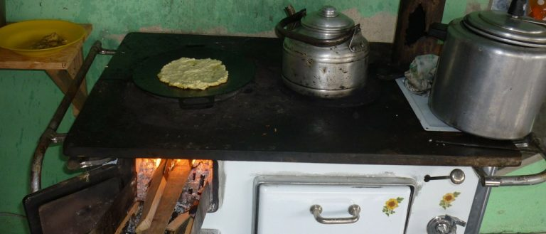 A wood stove cooking tea and bread.