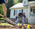 Spectrm volunteers dig holes for the ramp posts May 19 during the build day with Asheville Habitat Home Repair.