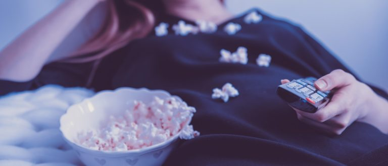A woman eating popcorn on a couch while watching television.