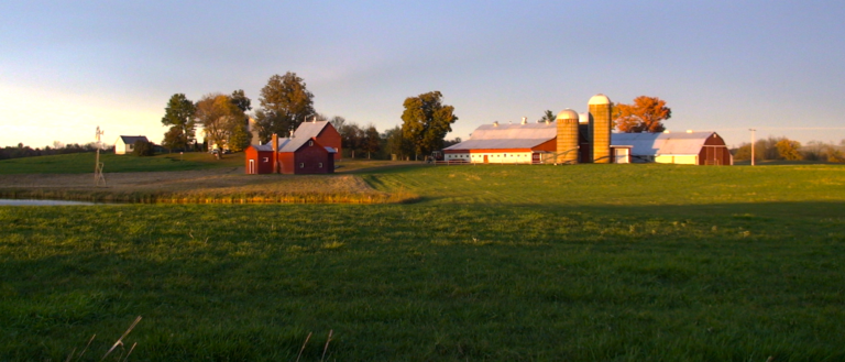 A wide view of a farm at dusk.