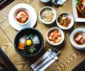 Korean kimchi and other dishes on a wooden table.