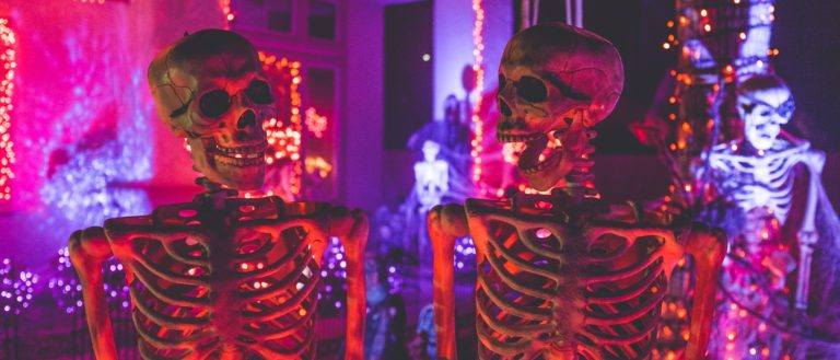 Skeletons in front of a neon-lit haunted house.