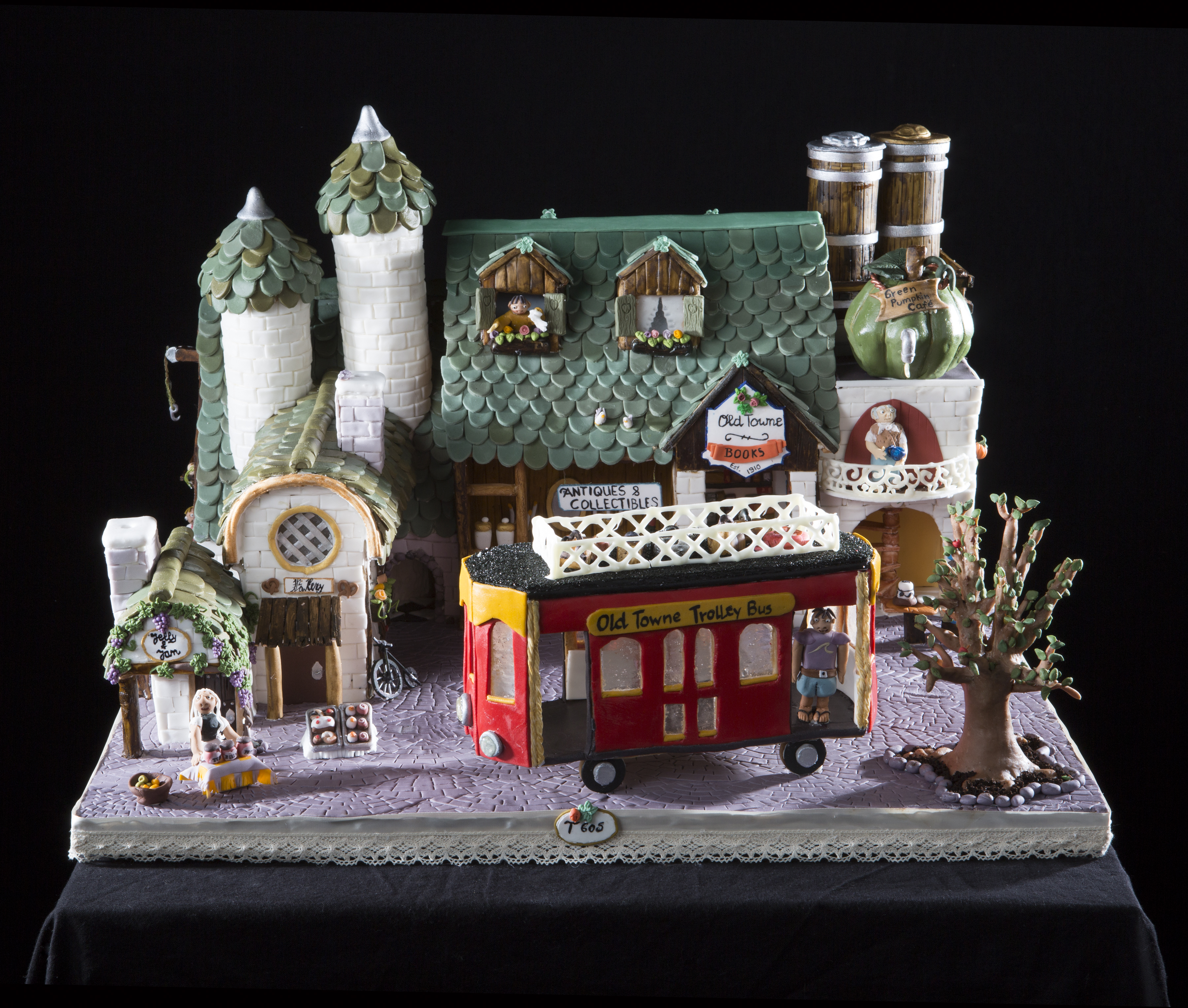 A gingerbread creation of a large green-roofed store with a trolley bus and tree in front.