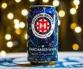 A can of Highland Brewing's Starchaser White in front of a Christmas tree.