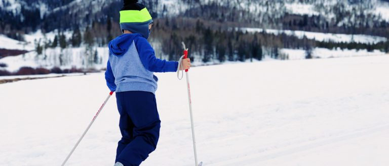 A child skiing up a small slope on a mountain.