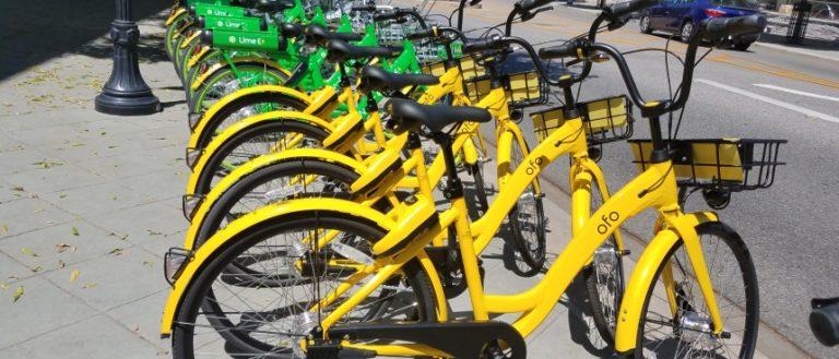 Several share bikes on a sidewalk.