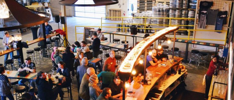 People having beer inside Hi-Wire Brewing's Asheville location.