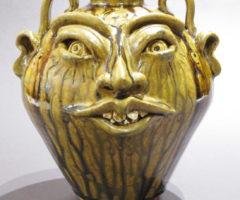 A yellow-hued face jug created by artist Kim Ellington.