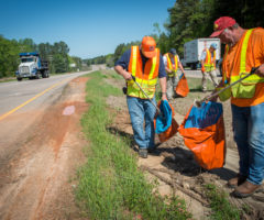 Volunteers cleaning up litter along a highway.