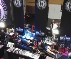 People receiving tattoos at a crowded tattoo convention floor.