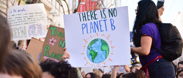 People downtown with signs raising awareness of climate change.