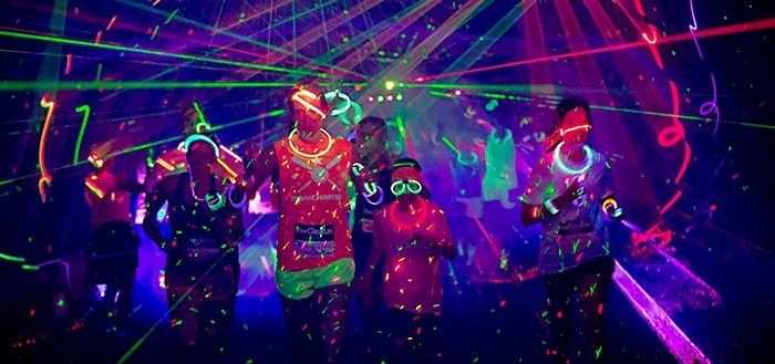 Runners participating in a glow in the dark 5K with bright strobes and colorful spray.