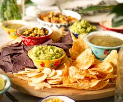 Chips, salda, and condiments on a table.