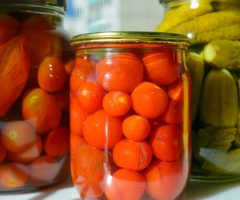 Tomatoes and pickles in canning jars.